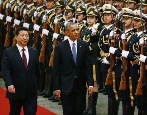 China's President Xi Jinping (L) walks with U.S. President Barack Obama (C) as they inspect the honour guards during a welcoming ceremony at the Great Hall of the People in Beijing, November 12, 2014. REUTERS/Petar Kujundzic